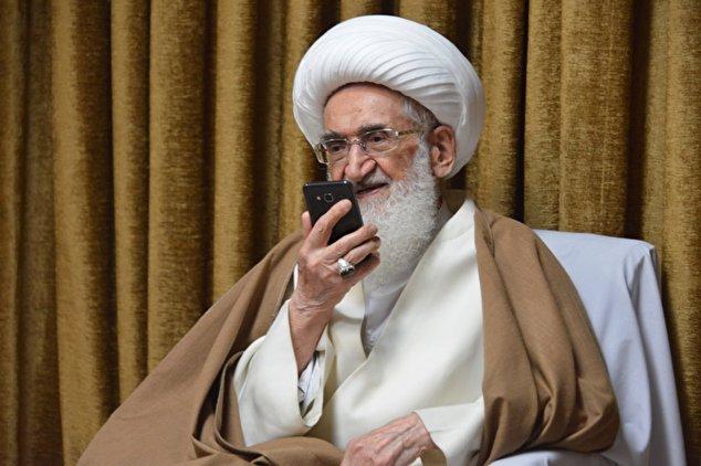 تصویر آیت الله نوری همدانی در حال صحبت با تلفن همراه هوشمند