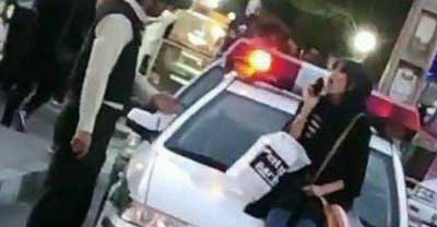 بازداشت زن جوانی که روی خودروی پلیس نشست + عکس