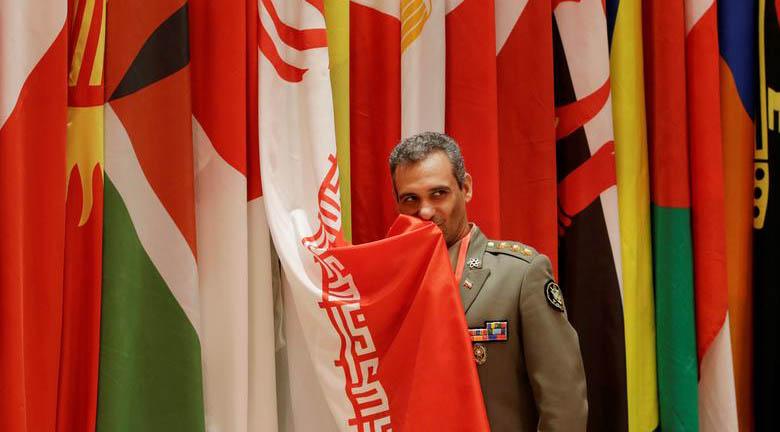 نظامی ایرانی در حال بوسیدن پرچم ایران در حاشیه اجلاس چین + عکس