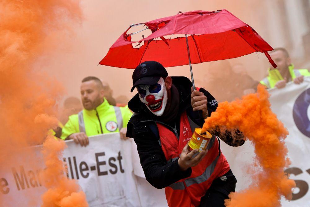 مردی با ماسک دلقک در تظاهرات عکس اصلاحات بازنشستگی در فرانسه
