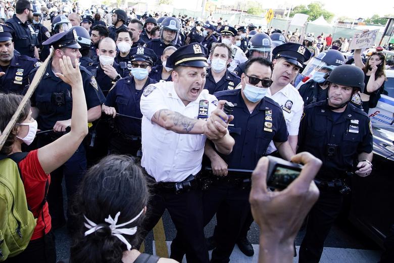 یک افسر پلیس آمریکا در حال پاشیدن اسپری بر روی معترضین + عکس