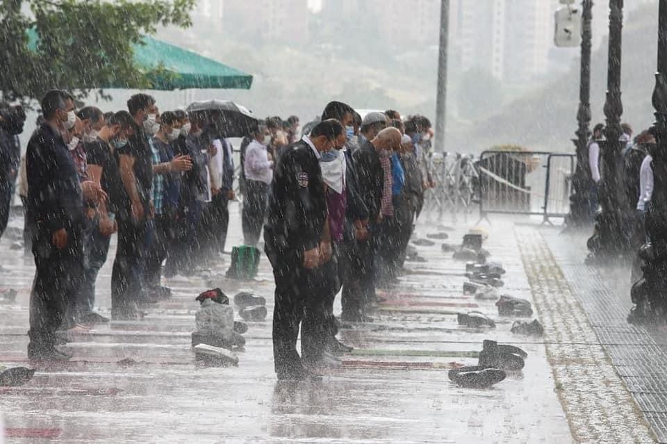اقامه نماز زیر بارش شدید باران + عکس