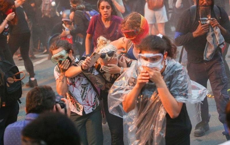فرار معترضان از گازهای اشک آور پلیس آمریکا + عکس