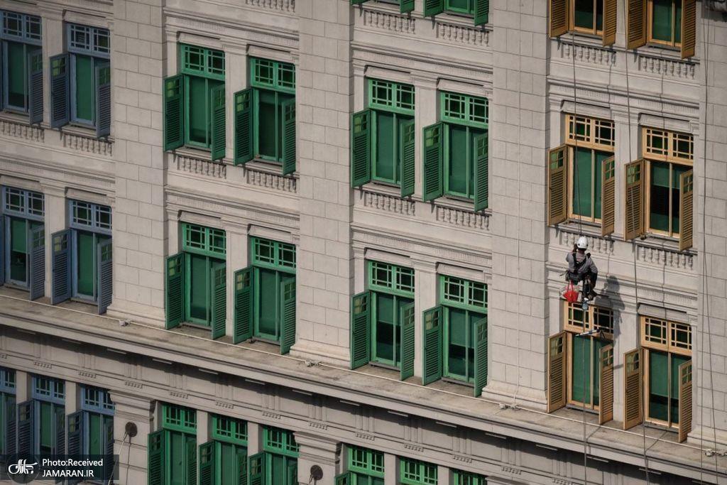 یک کارگر در حال تمیز کردن نمای ساختمان وزارت ارتباطات + عکس