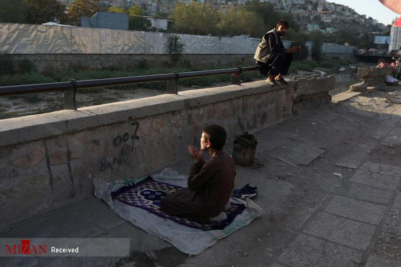 نماز و آرامش کودک افغانستانی در هیاهوی خیابان های کابل + عکس