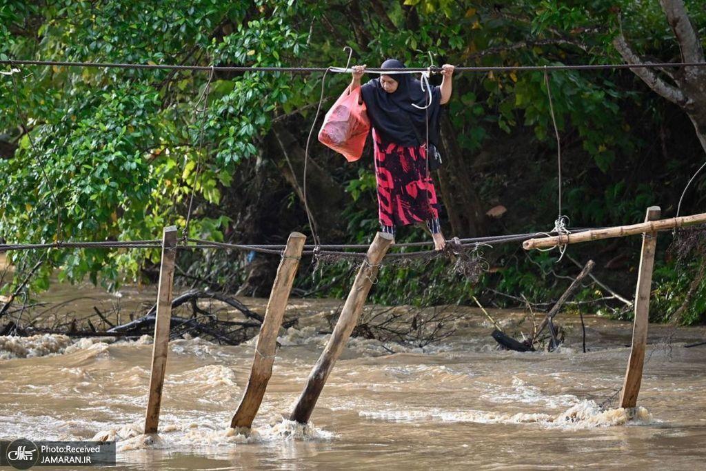 عبور با مشقت از بقایای یک پل روی رودخانه + عکس