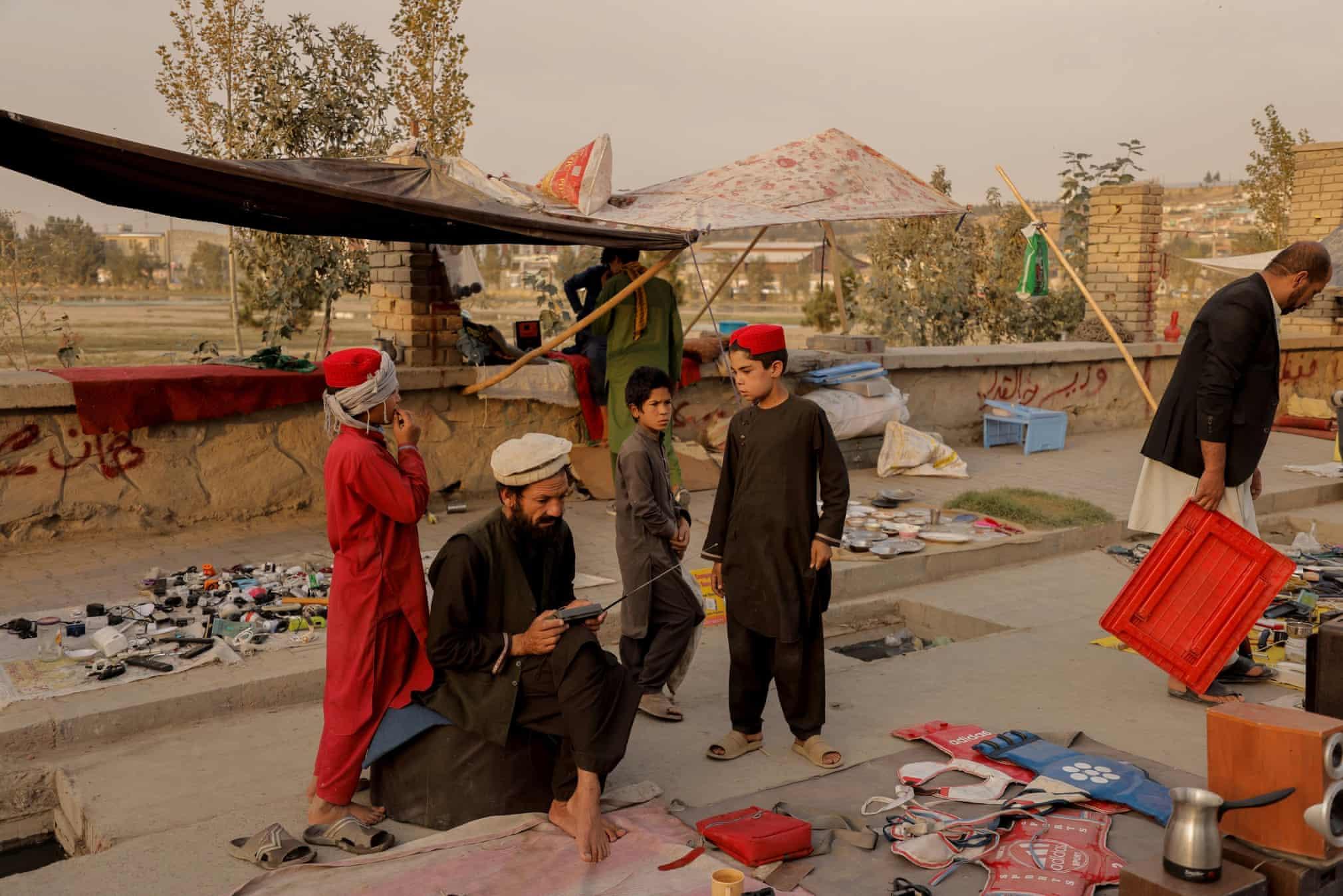 خانواده ای افغان در حال فروش وسایل منزل برای خروج از کشور + عکس