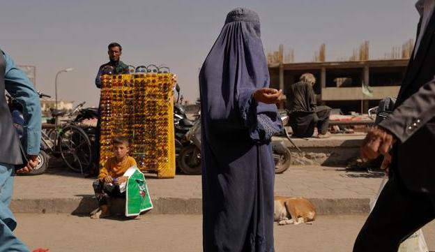 نیازمندی زن برقع پوش افغان و کودکش در کنار خیابان + عکس