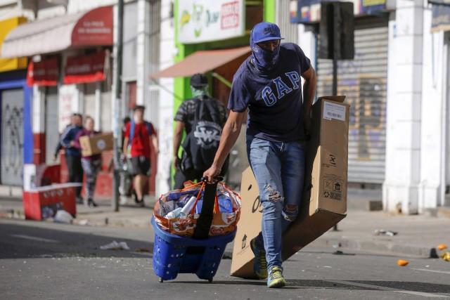 غارت فروشگاه ها توسط معترضان در شیلی + عکس
